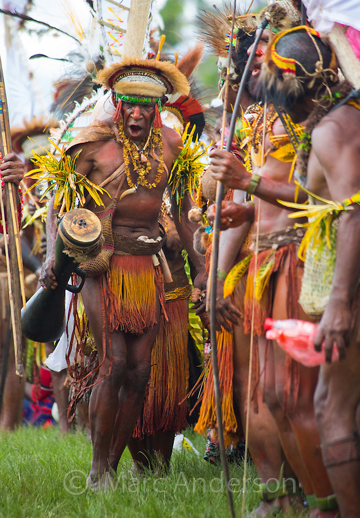 Man holding a drum and dancing in a group at the Goroka show in the highlands of Papua New Guinea.