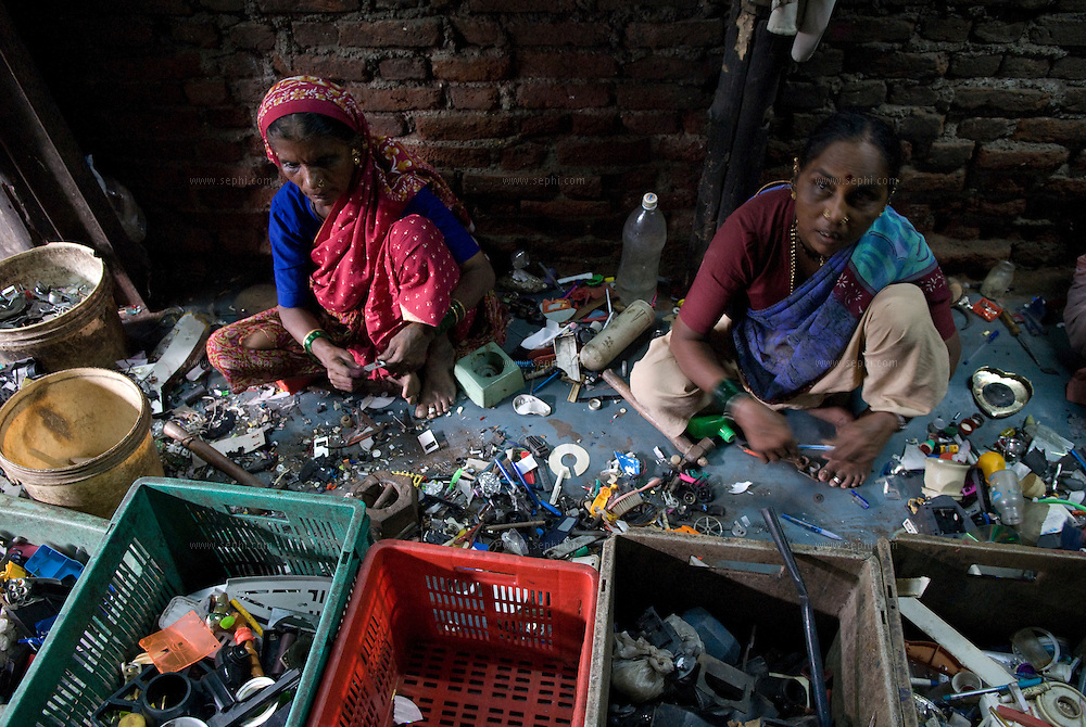 women seperate componenets from discarded electrical devices into boxes in one of the recycling shacks in Dharavi's industrial area.