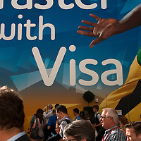 Visitors walk past a visa advertisement on the way to a technical rehearsal for the Olympic Opening Ceremony for the 2012 Olympic Games, at the Olympic stadium, London.