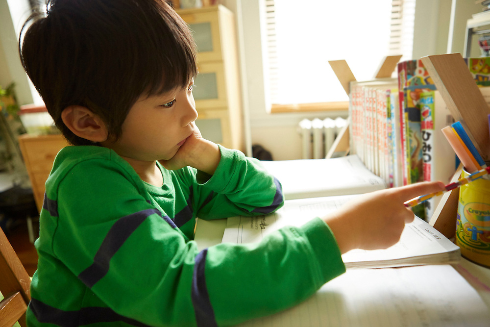 Portrait photograph of a Japanese boy who is bored of doing homework