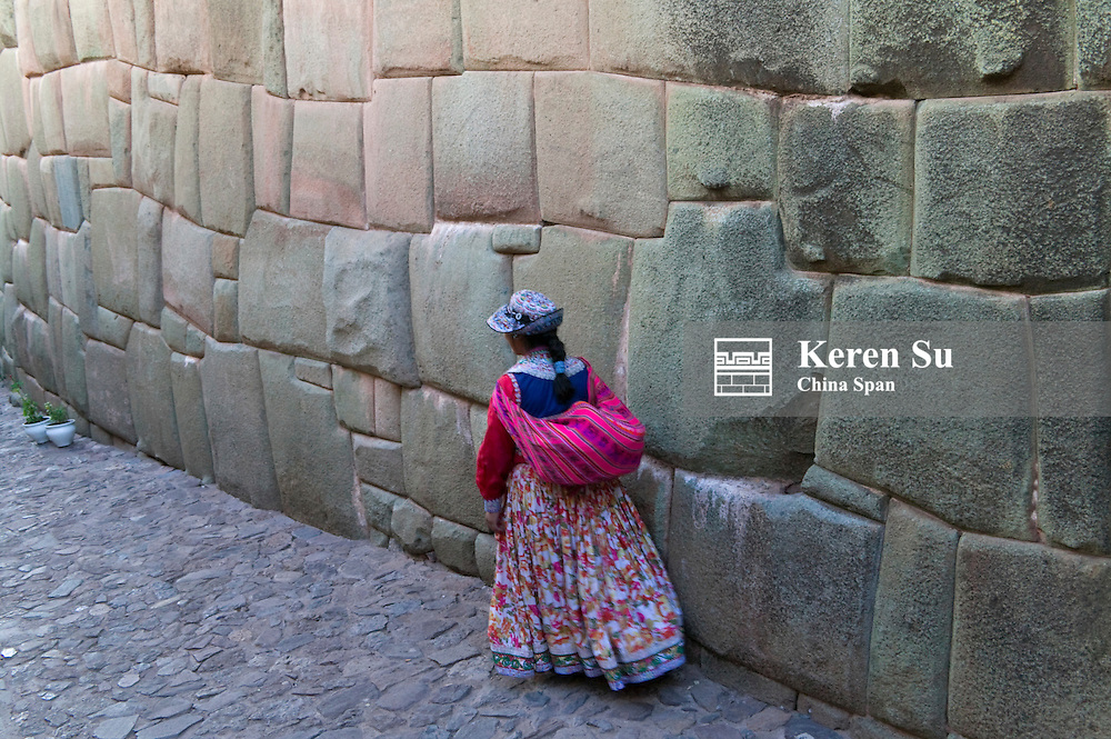Indian woman on cobble stone street lined with Inca walls of polygonal stones, Cuzco, Peru