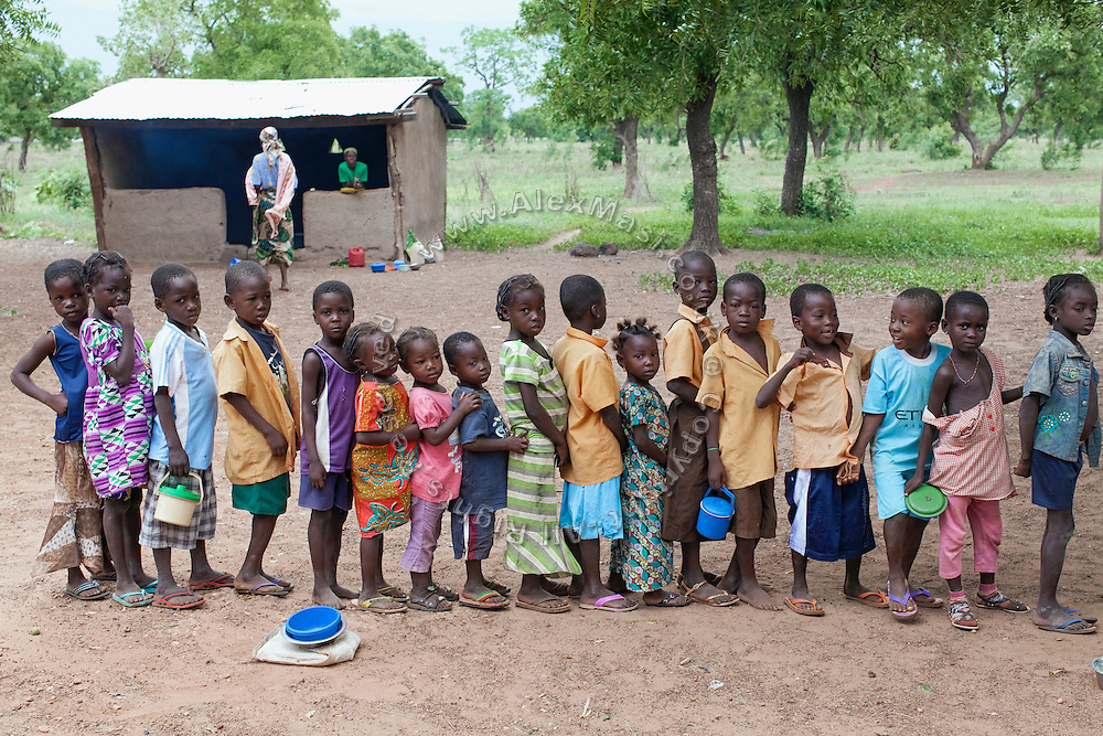 Pupils attending Boggu Primary School are standing in a line while waiting for a nutritional meal available under the School Feeding Program run by the local NGO SEND, in the courtyard of the small rural institution that Hassana Ibrahim, 11, is attending, in Boggu, Tamale, northern Ghana.