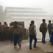 School children at TCV, the Tibetan Children's Village. McLeod Ganj, Dharamsala, India. 7/29/05. In the rolling  fog one can barely make out the school's motto: Come to Learn, Go to Serve. The school educates not only the Tibetan children born in exile, but also those that continue to arrive each year after a perilous escape over the Himalayan Mts from Tibet.