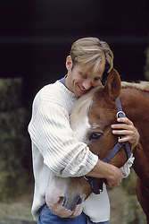 man hugging a horse