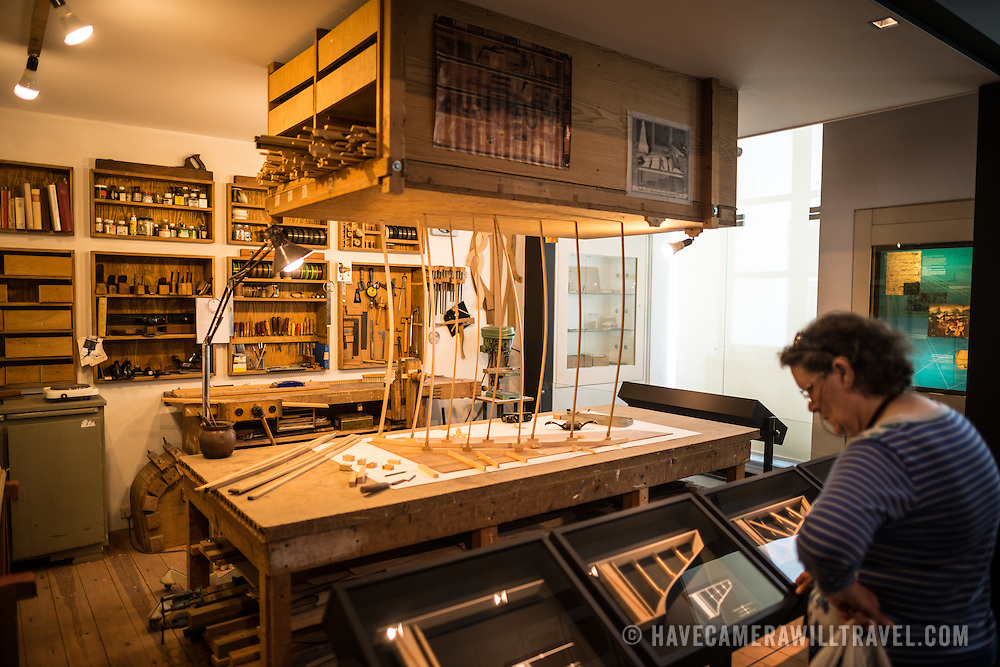 A visitor looks at a traditional piano workshop on display at the Musical Instrument Museum in Brussels. The Musee des Instruments de Musique (Musical Instrument Museum) in Brussels contains exhibits containing more than 2000 musical instruments. Displays include historical, exotic, and traditional cultural instruments from around the world. Visitors to the museum are given handheld audio guides that play musical demonstrations of many of the instruments. The museum is housed in the distinctive Old England Building.