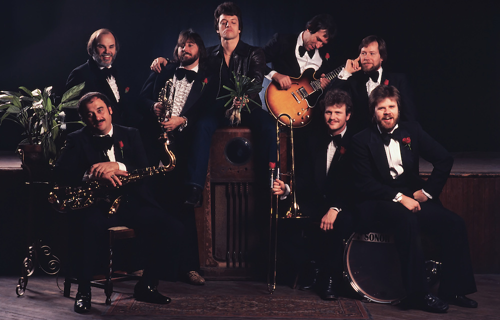Green Onions Rhythm and Blues Revue at Fitzgerald's music venue in Houston, TX. All the members are dressed in tuxedos with a red rose in each of their lapels. Some instuments in the picture includes saxaphone, trombone, and bass guitar