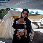 Hanan, 33, from Idlib, Syria, holding her son, Ahmed, 25 days, the youngest refugee in Ritsona refugee camp. Greece, July, 2016.