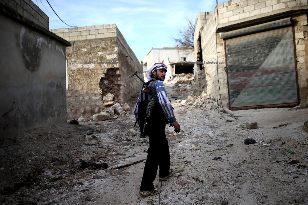 A soldier of the Free Syrian Army inspects a little road in Kureen after battle tanks have devastated the houses by driving through this too small lane. On 22. February the syrian army attacked the village of Kureen, Province of Idlib, Syria. Kureen was among the first villages in the northwest of Syria controlled by the opposition. Some villagers and members of the defence units escaped to surrounding olive orchards, when the attack begun in the early morning. A majority of the inhabitants didn´t manage to escape. The heavy shelling lasts 7 houres. Soldiers searched all houses, burnt some of them down, loote shops, stole cars and furniture. About 60 motorcycles were burnt down. Tanks demolished several houses. 6 men were executed. One woman died as a result of an heart attack.