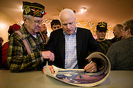 Sen. John McCain (R-AZ) signs a poster for Robert Lynn, a Navy veteran, at a campaign stop in Bridgewater, NH, on Tuesday, Jan. 1, 2008.