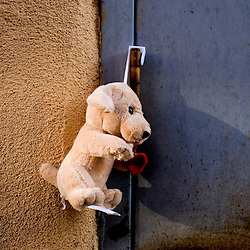 A stuffed animal hangs from the hinge of a door in an alleyway.