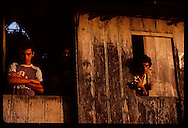 Rubber tappers peering out from their wooden shack at sunrise in the Amazon; Brasileia, Acre. Brazil