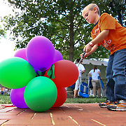 09/30/12 - Newark, DE - The Taste of Newark - Christopher Kent (7) pops ballons during the clean up efforts at The Taste of Newark event at Old College Lawn on the University of Delaware main campus Sunday, Sept. 30 2012, in Newark DE. ..SAQUAN STIMPSON/Special to The News Journal