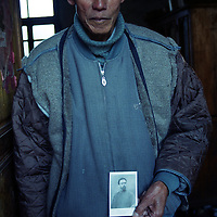 """CIZHONG, DECEMBER 17, 2000: Bernard, 75, holds a picture of Maurice Tournay,one of the French missionaries who built the Catholic church in Cizhong at then end of the 19th century, Yunnan province , December 17, 2000. Bernard went to jail for 22 years after the foreign missionaries left Cizhong in 1952 for having assisted them . he passed away in 2003..The church in Cizhong is believed to be the real life model for James Hilton's famous novel """" lost Horizon""""- a description of Shangri-La-..Maurice Tournay is one of the catholic martyrs who were canonized by pope John Paul II on October 1, 2000.. ."""