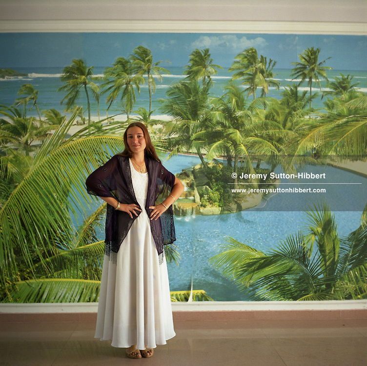 Garoafa, a young married Roma woman, stands in front of a poster with a tropical scene, in her new home. These photo-posters have become popular within the camp, replacing the painted murals that used to adorn the walls of the Roma houses..
