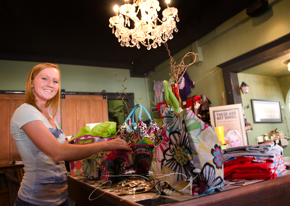 Sales associate Hannah Boatwright arranges Room It Up purses and handbags at the Funky Monkey gift shop Oct. 10, 2011 in Holly Springs, Miss. The store, located inside Tyson Drug. Co., features a number of gift items from Mississippi artisans. (Photo by Carmen K. Sisson/Cloudybright)