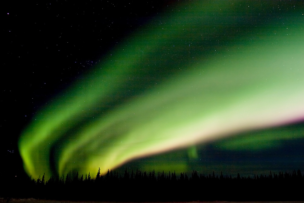A curtain of green northern lights dances across the sky.