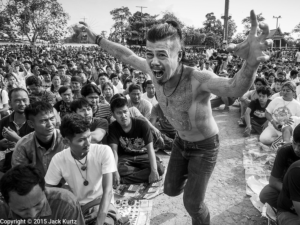 "07 MARCH 2015 - NAKHON CHAI SI, NAKHON PATHOM, THAILAND:  A man channeling the power of his sacred tattoo rushes the stage at the Wat Bang Phra tattoo festival. Wat Bang Phra is the best known ""Sak Yant"" tattoo temple in Thailand. It's located in Nakhon Pathom province, about 40 miles from Bangkok. The tattoos are given with hollow stainless steel needles and are thought to possess magical powers of protection. The tattoos, which are given by Buddhist monks, are popular with soldiers, policeman and gangsters, people who generally live in harm's way. The tattoo must be activated to remain powerful and the annual Wai Khru Ceremony (tattoo festival) at the temple draws thousands of devotees who come to the temple to activate or renew the tattoos. People go into trance like states and then assume the personality of their tattoo, so people with tiger tattoos assume the personality of a tiger, people with monkey tattoos take on the personality of a monkey and so on. In recent years the tattoo festival has become popular with tourists who make the trip to Nakorn Pathom province to see a side of ""exotic"" Thailand.   PHOTO BY JACK KURTZ"