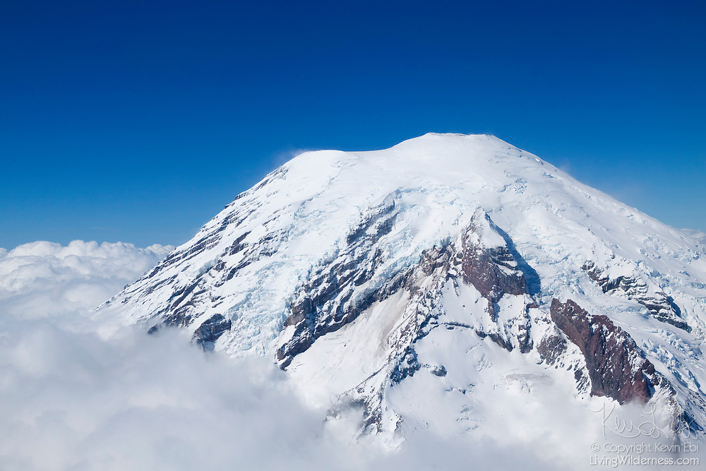 The base of Mount Rainier is covered by a thick layer of low clouds. Rainier, at 14,411 feet (4,392 m), is the highest peak in the Cascade Range.