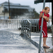 Carli Marie Kocjancic holds onto a street sign while playing in the storm surge generated by Tropical Storm Alberto as the waves break on to a road in Cedar Key, Florida June 13, 2006. REUTERS/Scott Audette