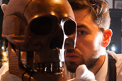"""London, March 4th 2015. Sotheby's in London hosts """"one of the most extraordinary collections of our time"""", an anonymous collector's vast assembly of fine art pieces, including skulls, bear sculptures, paintings and installations. PICTURED: A Sotheby's technician examines a theatrical prop skull made of walnut and bamboo, which is expected to fetch £800 - £1,000 at auction."""