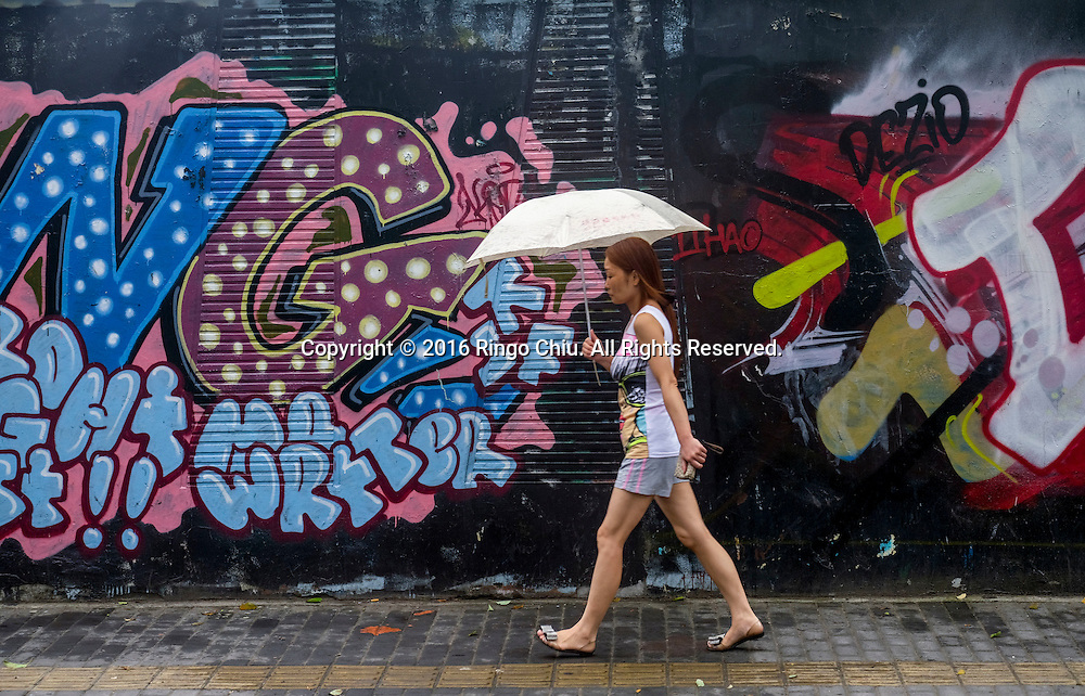 A woman with an umbrella walks by murals near the M50 Art Colony in Shanghai, China. Shanghai is the most populous city in China and the most populous city proper in the world. It is one of the four direct-controlled municipalities of China, with a population of more than 24 million as of 2014. It is a global financial centre, and a transport hub with the world's busiest container port. Located in the Yangtze River Delta in East China, Shanghai sits on the south edge of the mouth of the Yangtze in the middle portion of the Chinese coast. The municipality borders the provinces of Jiangsu and Zhejiang to the north, south and west, and is bounded to the east by the East China Sea. A major administrative, shipping, and trading town, Shanghai grew in importance in the 19th century due to trade and recognition of its favourable port location and economic potential. The city was one of five forced open to foreign trade following the British victory over China in the First Opium War while the subsequent 1842 Treaty of Nanking and 1844 Treaty of Whampoa allowed the establishment of the Shanghai International Settlement and the French Concession. The city then flourished as a center of commerce between China and other parts of the world (predominantly Western countries), and became the primary financial hub of the Asia-Pacific region in the 1930s. However, with the Communist Party takeover of the mainland in 1949, trade was limited to socialist countries, and the city's global influence declined. In the 1990s, the economic reforms introduced by Deng Xiaoping resulted in an intense re-development of the city, aiding the return of finance and foreign investment to the city. Shanghai has been described as the &quot;showpiece&quot; of the booming economy of mainland China; renowned for its Lujiazui skyline, museums and historic buildings, such as those along The Bund, the City God Temple and the Yu Garden.(Photo by Ringo Chiu/PHOTOFORMULA.com)<br /> <br /> Usage Notes: This content is intended for edi