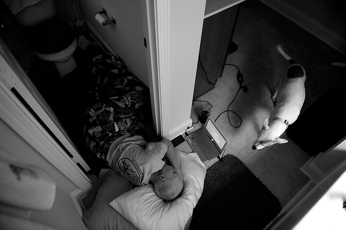 Sick and unable to get off the bathroom floor, Keri is kept company by her dog Scamp as she recuperates from a shot given to her to help her blood counts recover after a chemo treatment. — © /
