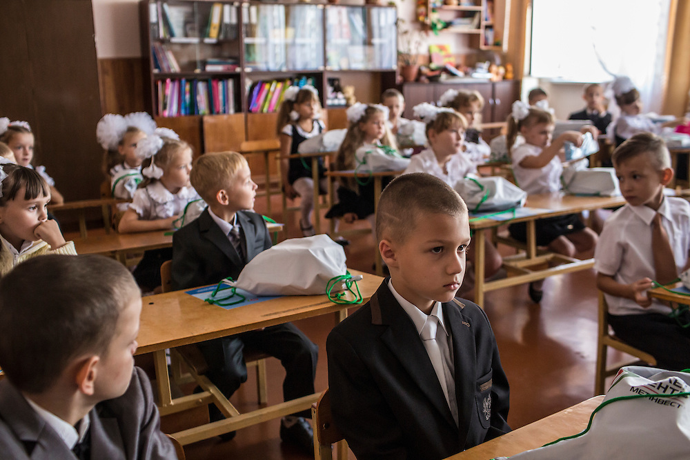 MARIUPOL, UKRAINE - SEPTEMBER 1, 2015: Students in the first class at School 68 arrive for the first day of the new school year in Mariupol, Ukraine. On January 24 of this year, shelling in the same neighborhood killed 31 people, all civilians, and while much recent fighting has been concentrated near Mariupol, a drop in ceasefire violations in the past few days has been credited to a desire to not interfere with the start of the new school year. CREDIT: Brendan Hoffman for The New York Times