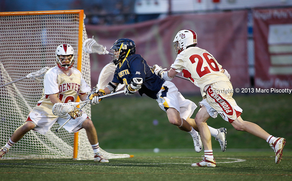 SHOT 4/5/13 6:24:21 PM - Marquette's Connor Bernal #49 attempts a diving backhanded shot in front of the University of Denver's Carson Cannon #26 and goalkeeper Ryan LaPlante #10during their NCAA Men's Lacrosse game at the Peter Barton Lacrosse Stadium on the University of Denver''s campus. The University of Denver won the game 15-4.(Photo by Marc Piscotty / © 2013)