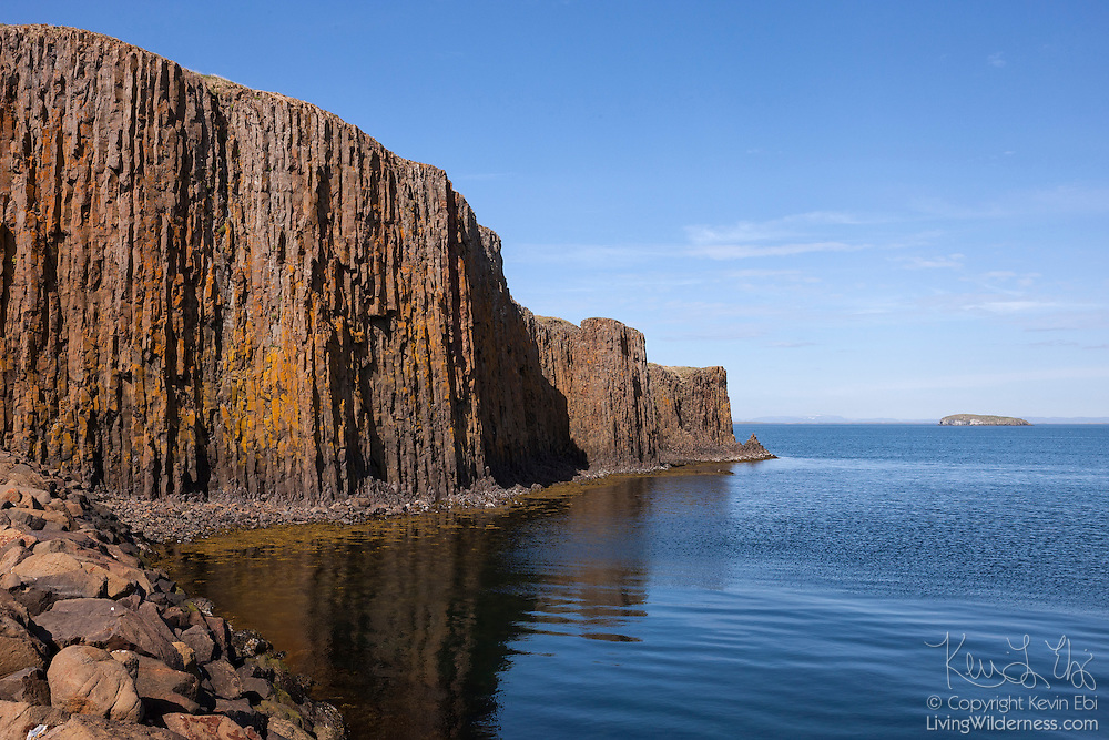 A towering columnar basalt cliff is partially reflected in the waters of Breiðasund in the town of Stykkishólmur, Iceland. Columnar basalt is a volcanic rock formed when basalt lava rapidly cools at or very near the Earth's surface. Basalt, which is naturally grey or black, is rich in iron and can rapidly rust, taking on a reddish-brown appearance.