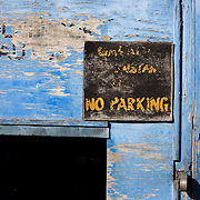 A fading and peeling sign that seen better days, still urges motorists not to park in front of this contantly-used garage entrance in South London, England.
