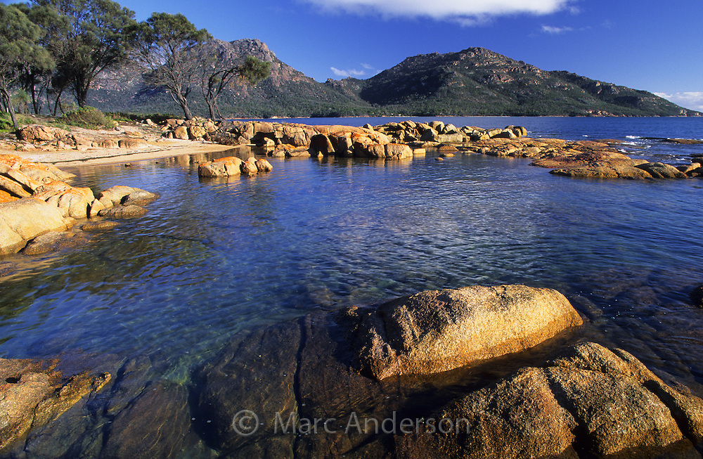 Rocky bay and coastland at Coles Bay, with the Hazards in the background, Freycinet Peninsula, Tasmania.