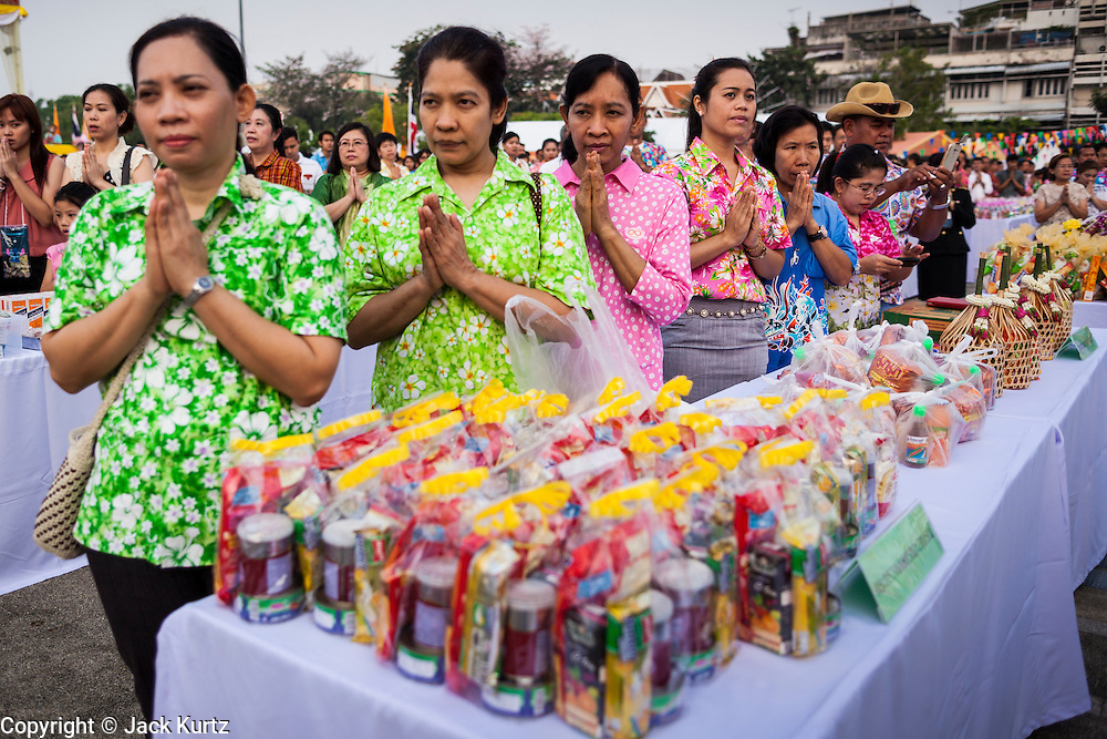 13 APRIL 2014 - BANGKOK, THAILAND:  People pray during a mass merit making ceremony for Songkran at Bangkok City Hall. Many people go to temples and religious ceremonies to make merit on Songkran. Songkran is celebrated in Thailand as the traditional New Year's Day from 13 to 16 April. Songkran is in the hottest time of the year in Thailand, at the end of the dry season and provides an excuse for people to cool off in friendly water fights that take place throughout the country. Songkran has been a national holiday since 1940, when Thailand moved the first day of the year to January 1.   PHOTO BY JACK KURTZ
