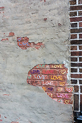 detail of exposed brick on a wall with the words LOVE written in colored paint