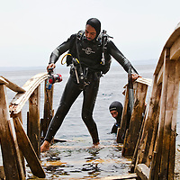"""A diver makes his way along a wooden bridge after diving in the Blue Hole outside of Dahab, Egypt. The Blue Hole is notorious for the number of diving fatalities which have occurred there, earning it the sobriquet """"World's Most Dangerous Dive Site"""" and the nickname """"Diver's Cemetery"""". The site is signposted by a sign that says """"Blue hole: Easy entry"""". Accidents are frequently caused when divers attempt to find the tunnel through the reef (known as """"The Arch"""") connecting the Blue Hole and open water at about 52 m depth. According to dive experts roughly 10 people die each year. April 2012."""