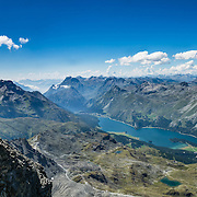"See Lake Segl from top station of Corvatsch cable car. Hike from Pontresina up Roseg Valley to Fuorcla Surlej for stunning views of Piz Bernina and Piz Rosegg, finishing at Corvatsch Mittelstation Murtel lift. Walking 14 km, we went up 1100 meters and down 150 m. Optionally shorten the hike to an easy 4 km via round trip lift. Pontresina is in Upper Engadine, in Graubünden (Grisons) canton, Switzerland, the Alps, Europe. The Swiss valley of Engadine translates as the ""garden of the En (or Inn) River"" (Engadin in German, Engiadina in Romansh, Engadina in Italian). This image was stitched from multiple overlapping photos."