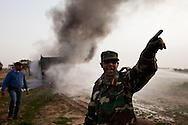 An army officer directs volunteers in the rebel army after a truck carrying weapons blew up near Benghazi on March 1, 2011.