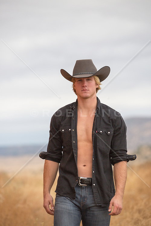 hot cowboy with an open shirt outdoors on a ranch
