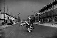 Young man uses a street of finished, completely unoccupied street of commercial properties to pop wheelies and do donuts with his dirtbike on the empty pavement.  The entire blocks lacks a single tenant.  In the northern part of the city of Xingtai in 2015 there are huge complexes, usually high-rise towers either standing unfinished or sparsely occupied.  Unfinished towers lack the frenetic construction crews working day and night.  Instead, a typical complex of 6 to 10 20+ storey towers will have small construction crews working in one or two of the towers while the rest will stand completely idle.  This is entirely new in a country that enjoyed double digit growth for three decades.  Xingtai, Hebei Province, China.
