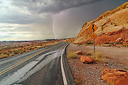 Lightning Striking from an afternoon thunderstorm in the Valley of Fire State Park in Nevada. The curvy road towards the storm highlights the foreboding atmosphere. Located outside of Las Vegas, Valley of Fire is Nevada's oldest and largest State Park.