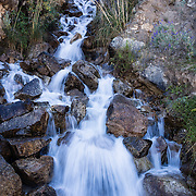 A waterfall plunges along the trail ascending into the Cordillera Blanca above Hualcayan village, in the Andes Mountains, Peru, South America. The photo is from our last day of 10 days trekking around Alpamayo in Huascaran National Park (UNESCO World Heritage Site).
