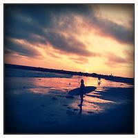 A  surfer stands on Venice Beach shore