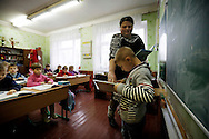 Arkadiy Yatsenko, 8 is called to the table to read a passage during a lesson at his school. He will go to Portugal were the same foster family hosts him and his sister for the 3th time.
