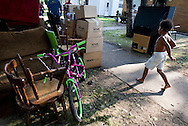 MILWAUKEE, WI — AUGUST 8, 2014: A child walks past piles of personal belongings on the curb during a tenant eviction at 4350 88th Avenue on the North Side of Milwaukee.