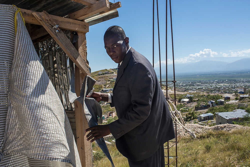 Luc Henry Pierre, the pastor at Church of God for Fighting Pentecostal Church on the edge of the Corail-Cesselesse camp for people displaced by the 2010 earthquake on Sunday, December 21, 2014 in Port-au-Prince, Haiti. The camp and surrounding areas are home to tens of thousands of people, many of whom live in makeshift shacks in a barren landscape with little or no access to jobs or resources.