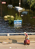 A woman drags a suitcase down the freeway past a flooded Welcome to New Orleans sign in downtown August 31, 2005. Authorities struggled on Wednesday to evacuate thousands of people from hurricane-battered New Orleans as food and water grew scarce and looters raided stores, while U.S. President George W. Bush said it would take years to recover from the devastation.