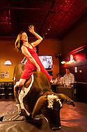 Woman, mechanical bucking bull, riding, Livingston Roundup Celebration, Montana