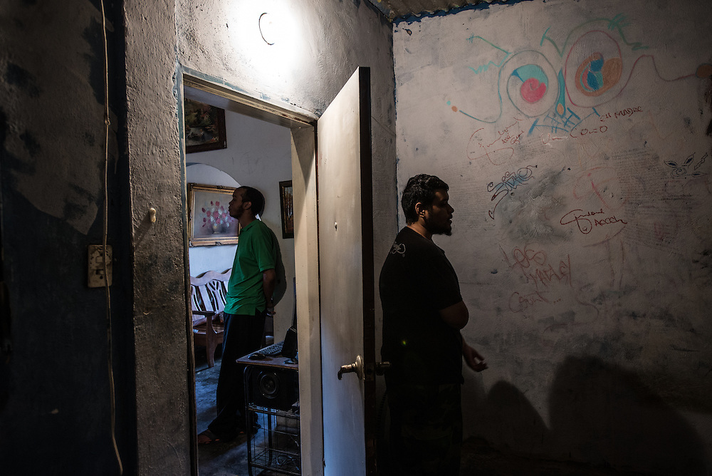 MARACAY, VENEZUELA - JULY 4, 2016: Schizophrenic patient, Accel Simione (right) raps one of the dozens of hip hop songs that he wrote on the walls of his bedroom for visitors, while his brother Gerardo, who is also schizophrenic, stands in the living room of their family home.  The economic crisis that has left Venezuela with little hard currency has already hit its health system, leaving hospitals without antibiotics, surgeons without gloves and patients dying on emergency room tables.  But beyond the hospital wards, thousands more mental health patients—many of whom had been living relatively normal lives at home with their families under medication—are slipping back into relapse for lack of basic psychiatric medications which control their symptoms, medical experts say. Accel and Gerardo both hear voices that urge them to commit violent acts. After three weeks without olanzapine, a drug used to control his paranoia, the voices inside Accel's head ordered him to kill his brother Gerardo.  When he refused, they ordered him to cut off his arm, and so he attacked himself. He took an electric circular saw from the family's garage, switched it on and began slicing into his arm. Soon his father found him and wrested the tool from his son's bloody hands. PHOTO: Meridith Kohut for The New York Times