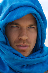 good looking man wrapped in blue fabric around his head