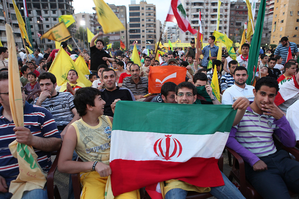 Supporters of the Shiite resistance and political group, Hizballah, rallied in the Dahiyeh southern suburbs of Beirut to watch a televised speech from Hizballah General Secretary Hassan Nasrallah. The rally was called for by Hizballah to celebrate Land Day, which is the 9th anniversary of Israel's withdrawal from southern Lebanon, which Hizballah and its supporters say was a victory over Israel. The rally comes just 13 days before Lebanese go to the polls to elect a new parliament. With Sunni Muslims and Shia Muslims mostly supporting their respective sectarian parties, Nasrallah praised Christian leader Michel Aoun. Aoun is head of the Free Patriotic Movement, which is allied with the Hizballah-led opposition March 8 coalition. ///Hizballah supporters holding an Iranian flag.