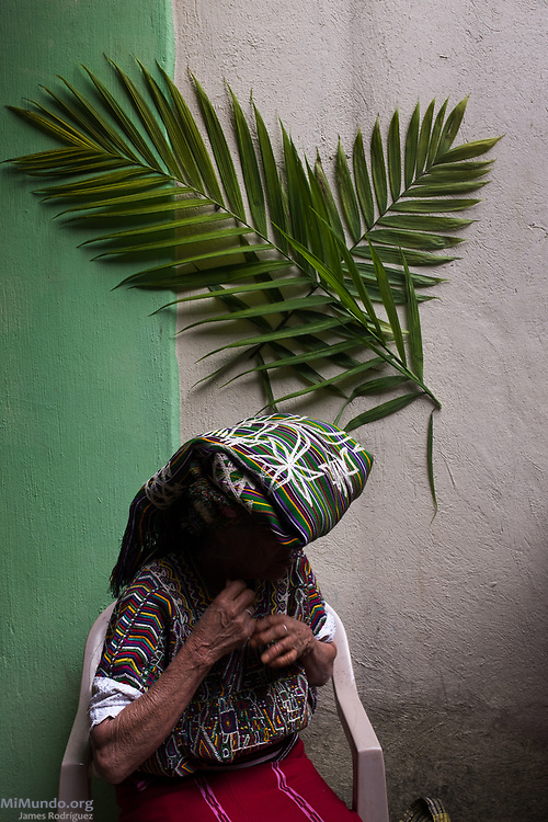 An Ixil Mayan woman awaits as residents of Nebaj gather to receive the human remains of 36 war victims. Most of the victims, exhumed from mass graves in Xe'xuxcap, near Acul, starved in the mountainside while fleeing State-led repression in 1982. Most of the remains, exhumed by members of the Forensic Anthropology Foundation of Guatemala (FAFG) in 2013, were identified using DNA analysis and buried 35 years after their death. Nebaj, Quiché, Guatemala. February 2, 2017.